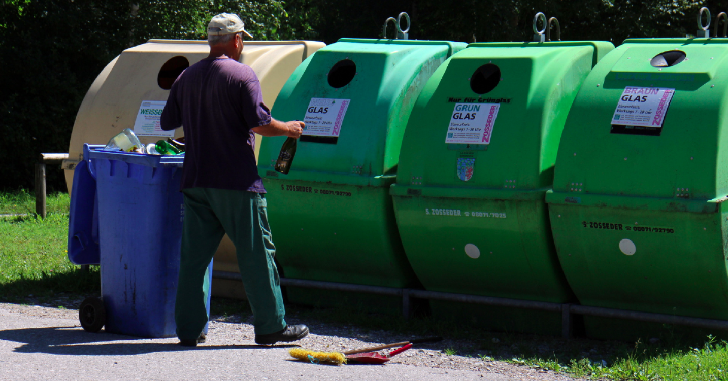 a man taking his rubbish to a row of green recycling bins