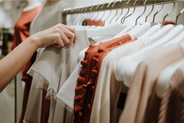 a hand selecting an item of clothing from a rack